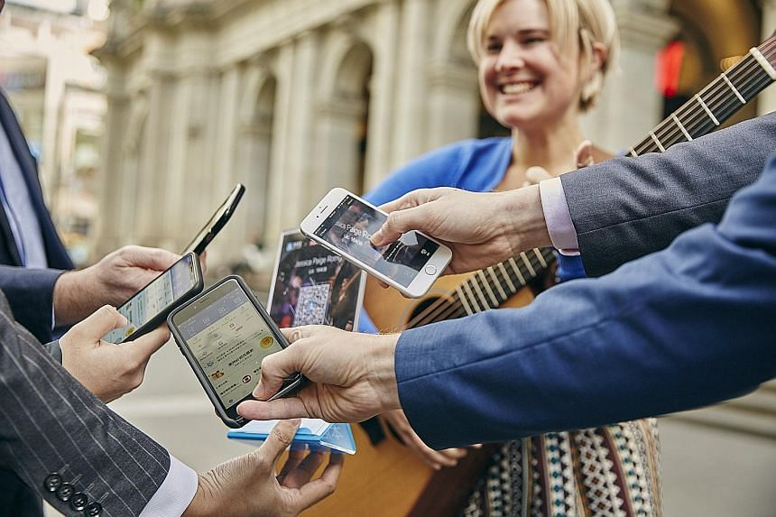"""Melbourne busker Jessica Paige can now accept donations from those who prefer to use """"tap-and-go"""" contactless payment or scan a QR code with their phones. Her income had fallen as fewer people carried cash."""