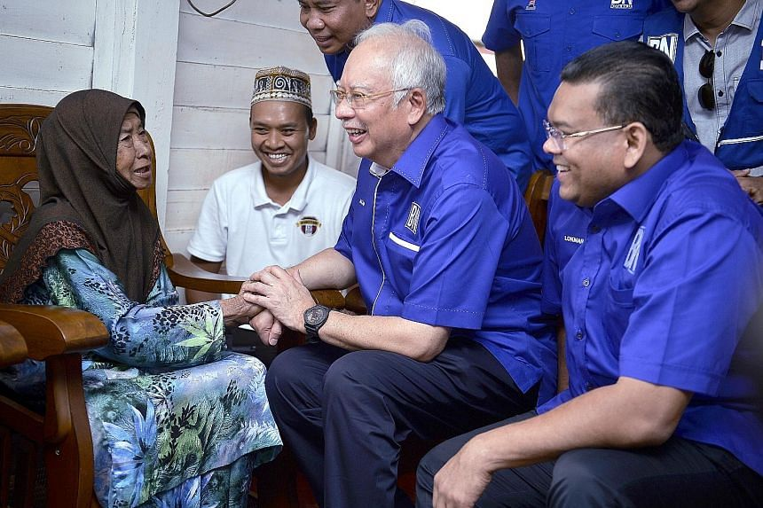 Former Malaysian prime minister Najib Razak (second from right) and Umno candidate Lokman Adam (right) meeting a resident of Sungai Kandis on July 25 while on the stump in the Selangor by-election. Parti Keadilan Rakyat candidate Mohd Zawawi Ahmad Mu