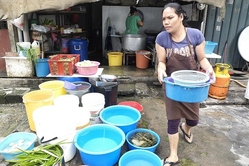A coffee-shop worker in Subang Jaya in Selangor storing water in containers during a water-rationing exercise. The Malaysian state's treated water reserves have been close to zero since 2015, which means taps run dry during droughts.