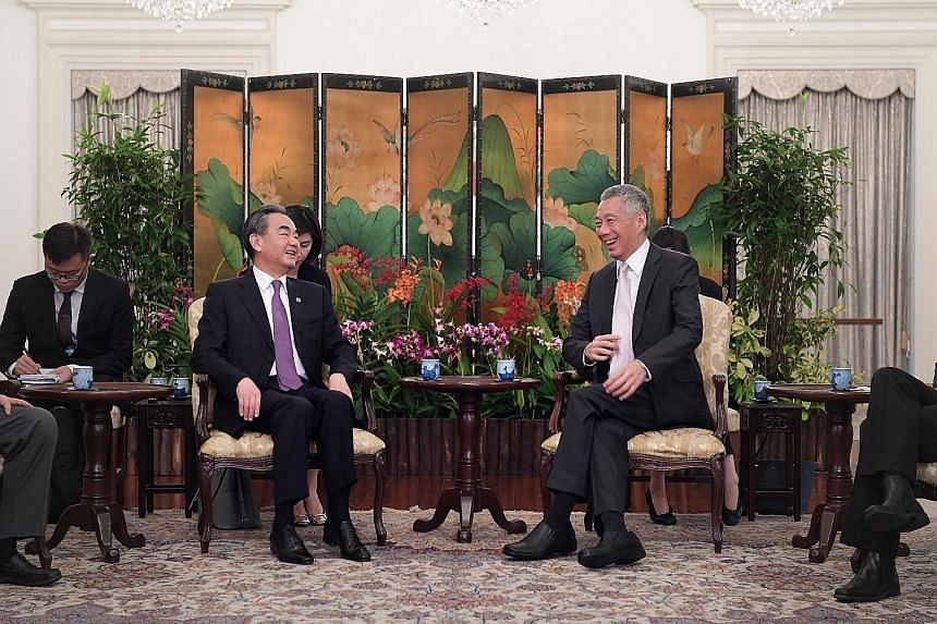 Left: Chinese Foreign Minister Wang Yi with Prime Minister Lee Hsien Loong at the Istana yesterday. They discussed key issues including the importance of maintaining stable Sino-US ties. Right: US Secretary of State Mike Pompeo calling on PM Lee yest