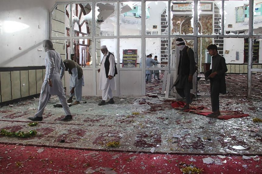 Afghan residents walking inside the damaged mosque after the suicide attack.
