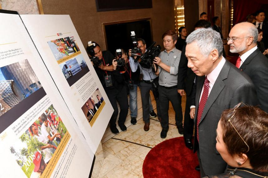 PM Lee Hsien Loong looks at key milestones from DBS' 50-year history. With him is DBS CEO Piyush Gupta.