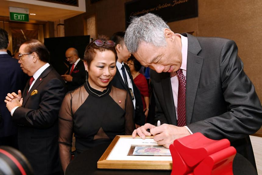 PM Lee signs on the frame of the commemorative gift of a $50 note that was in circulation in 1968, the year DBS was established. With him is Karen Ngui, Head of Group Strategic Marketing and Communications.