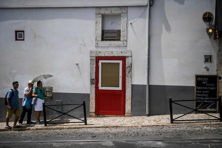 A tourist holds an umbrella to protect herself from the sun at Alfama neighborhood in Lisbon on Aug 3, 2018.