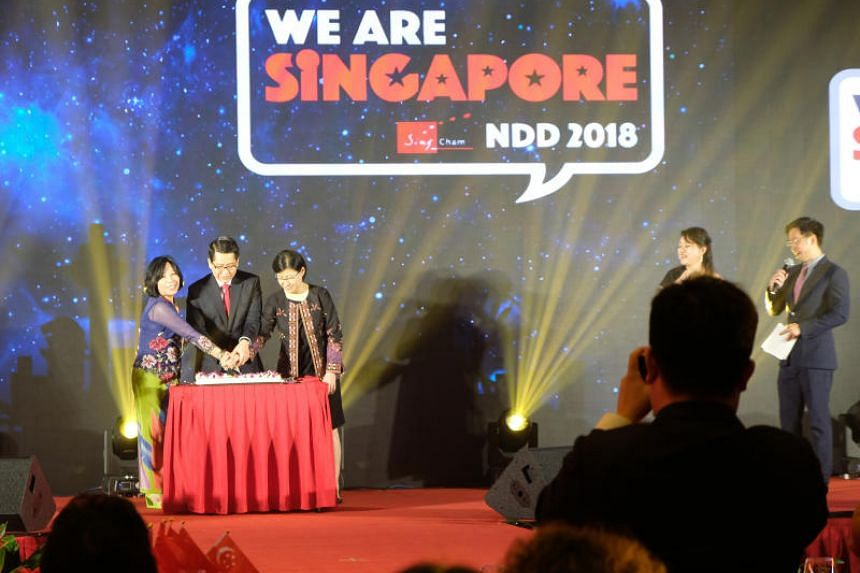 (From left) Singapore Chamber of Commerce and Industry in China (SingCham) chair Dorothy Seet, Ambassador Stanley Loh and his wife Mrs Kim Loh cut a birthday cake at the annual SingCham National Day Dinner in Beijing.