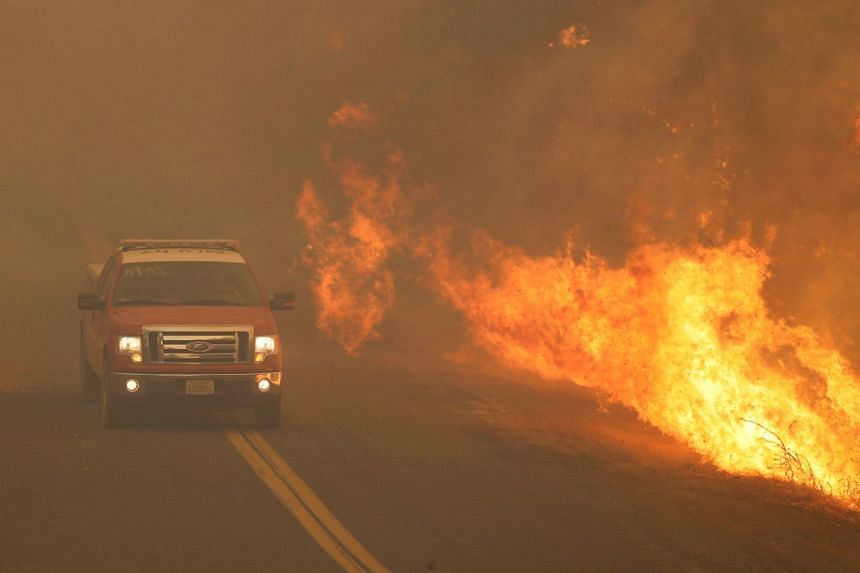 A firetruck rushes past flames that overran a road at the River Fire (Mendocino Complex) in Lakeport, California