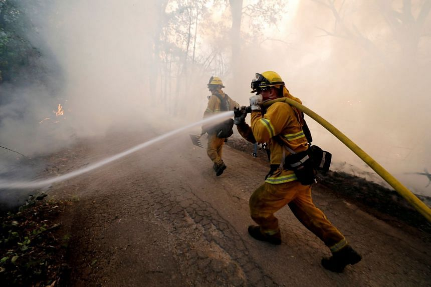 A firefighter knocking down hotspots to slow the spread of the River Fire (Mendocino Complex) in Lakeport, California.