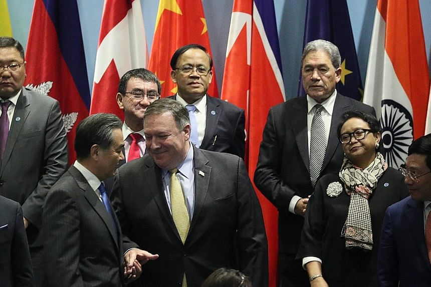 US Secretary of State Mike Pompeo shaking hands with Chinese Foreign Minister Wang Yi at the East Asia Summit foreign ministers' meeting yesterday. The 25th Asean Regional Forum Retreat session being held at the Singapore Expo yesterday.