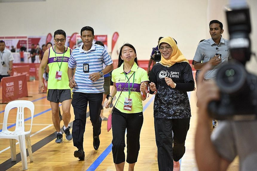 President Halimah Yacob taking on the guide's role for visually impaired runner Patricia Poo during the Inclusive Sports Festival at the Singapore Sports Hub yesterday. The festival offers the public a chance to experience how para-athletes compete i