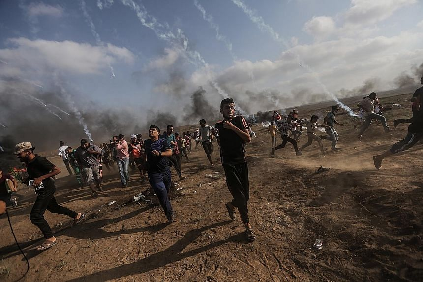 Palestinian demonstrators clashing with Israeli forces in the northern Gaza Strip on Friday, one of several spots where some 8,000 Gazans had gathered in a bid to sabotage the Israeli border fence. Two Palestinians were killed by Israeli fire during