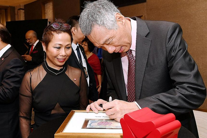 Above: PM Lee signing the frame of a commemorative gift of a $50 note that was in circulation in 1968, the year DBS was established. With him is head of group strategic marketing and communications Karen Ngui. Left: DBS chairman Peter Seah (far left)