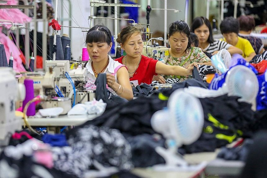 Workers at a swimwear factory in Jinjiang, in China's eastern Fujian Province. Speaking on the sidelines of a regional forum in Singapore yesterday, Chinese State Councillor and Foreign Minister Wang Yi said that China's threat of retaliatory tariffs