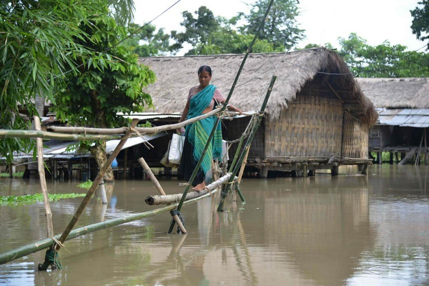 A villager uses a makeshift bamboo bridge to cross flood waters at Bongkuwal village in Golaghat, some 260km from Guwahati, Assam, on Aug 4, 2018.