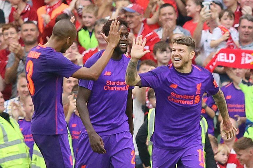 Liverpool's Spanish defender Alberto Moreno (R) celebrates scoring their fifth goal.