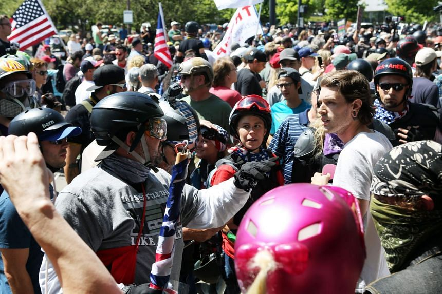 An alt-right sympathiser (left) knocks the hat off an opponent's head.