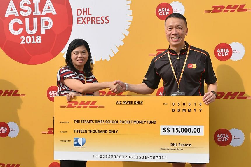 Ms Tan Bee Heong, general manager of The Straits Times School Pocket Money Fund, receiving a cheque from Mr Ken Lee, chief executive of DHL Express Asia Pacific.