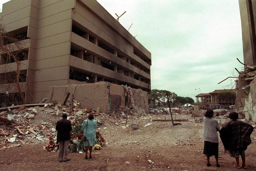 A file photo taken on Aug 9, 1998, shows Kenyan residents looking at the US embassy two days after a bomb blast that killed at least 280 Kenyans and 12 Americans.