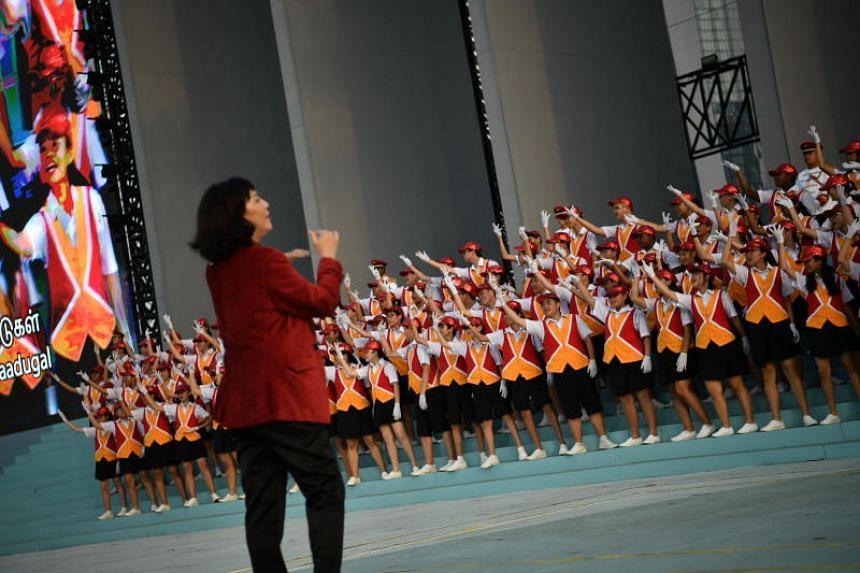 Conducting this year's combined school choir is Ms Lim Jiuan, 59, who teaches at Nan Hua High School.