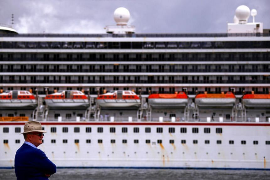 A tourist looks at the Carnival Legend cruise ship docked at the Overseas Passenger Terminal at Sydney's Circular Quay on March 8, 2017.