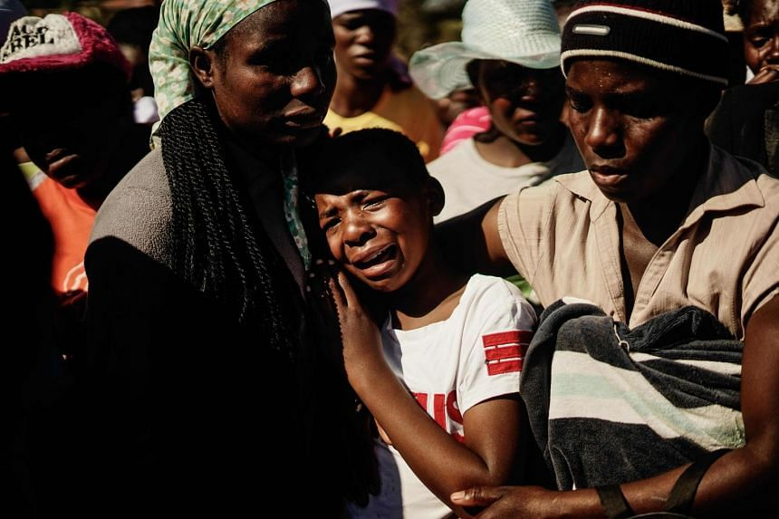 Ahlia Kumire (centre), daughter of Ishmael Kumire, reacts during her father's funeral ceremony.