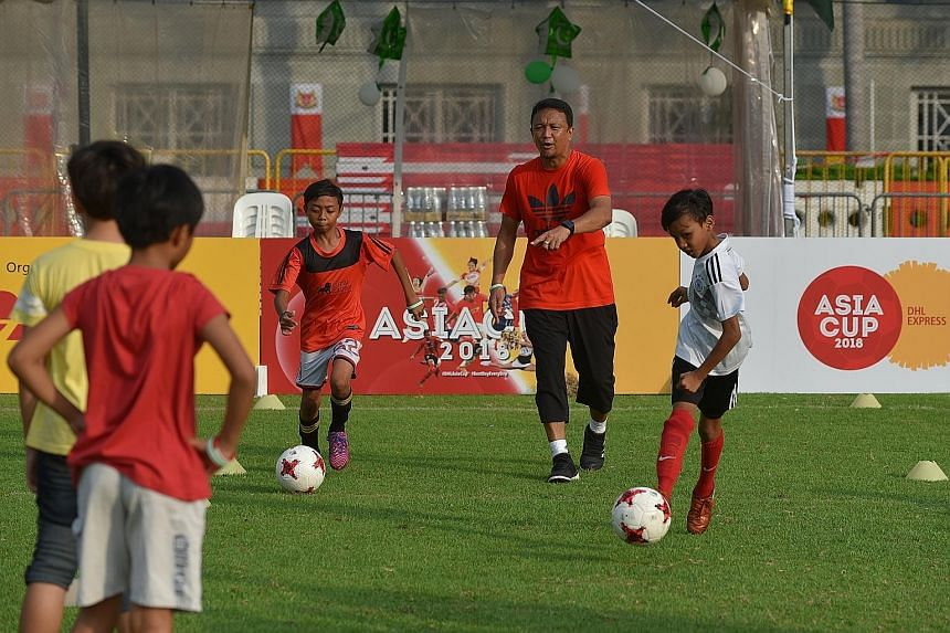Fandi Ahmad conducting a football clinic for 20 Straits Times School Pocket Money Fund beneficiaries yesterday.