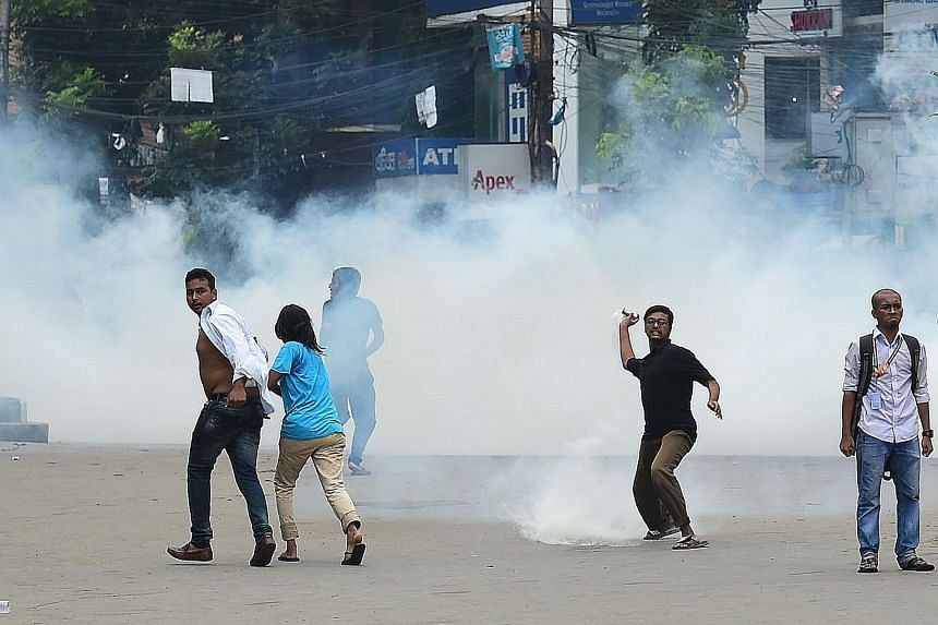 A Bangladeshi protester hurling back a tear gas shell fired by the police during a student protest in Dhaka yesterday. Images of attacks on students have flooded social media, prompting renewed anger.