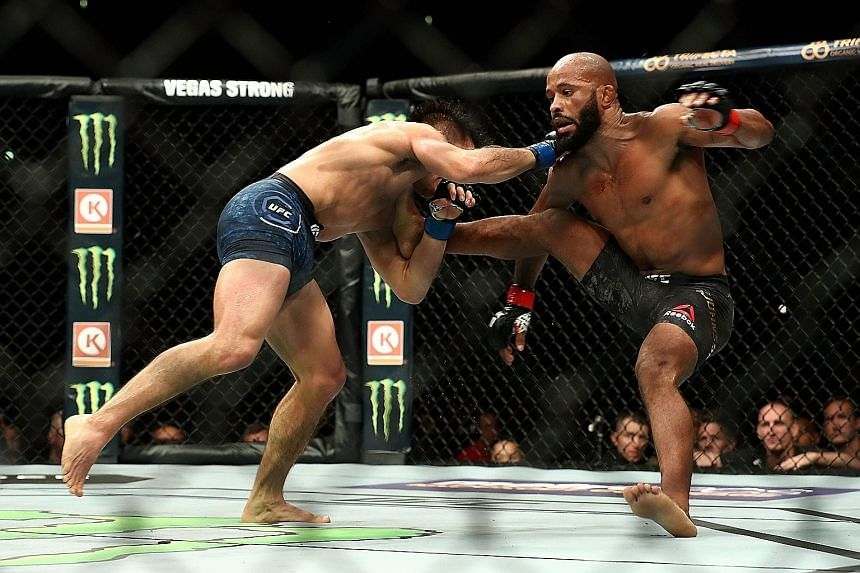 Demetrious Johnson is taken to the ground by Henry Cejudo in the fourth round of the UFC flyweight title bout during UFC 227 at Staples Center on Saturday in Los Angeles.
