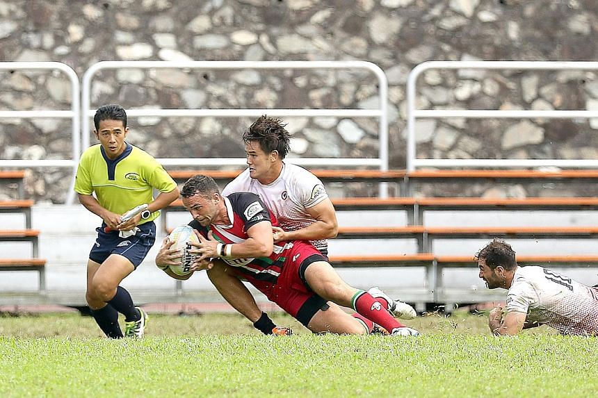 Singapore's Declan Martens (in white) attempts to stop his United Arab Emirates rival from scoring a try at the Asia Rugby Sevens Trophy final yesterday at the Queenstown Stadium.