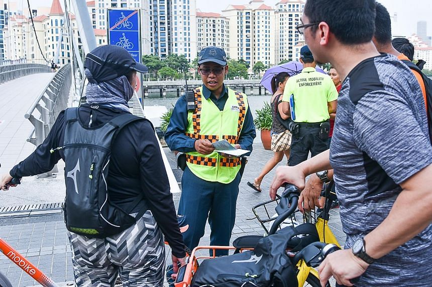 Auxiliary police officer Muhammad Hanafi Azeman, 27, sharing information on the Active Mobility Act with cyclists in Tanjong Rhu on Saturday. The officers are deployed alongside the Land Transport Authority's Active Mobility Enforcement Officers.