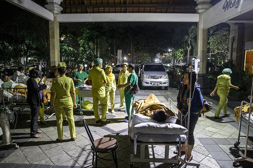 Hospital staff with patients evacuated from the hospital building after the magnitude-7 earthquake was felt in Denpasar, Bali, yesterday.