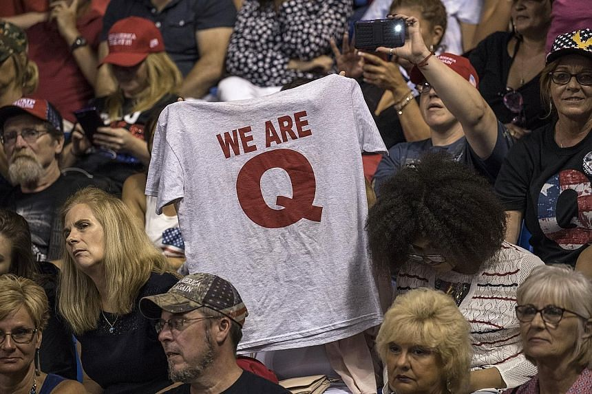 """A T-shirt with the words """"We Are Q"""" being held up before the start of US President Donald Trump's rally last Thursday in Wilkes-Barre, Pennsylvania. The news cycle about QAnon, sparked by its believers' visibility, is the best thing to ever happen to"""