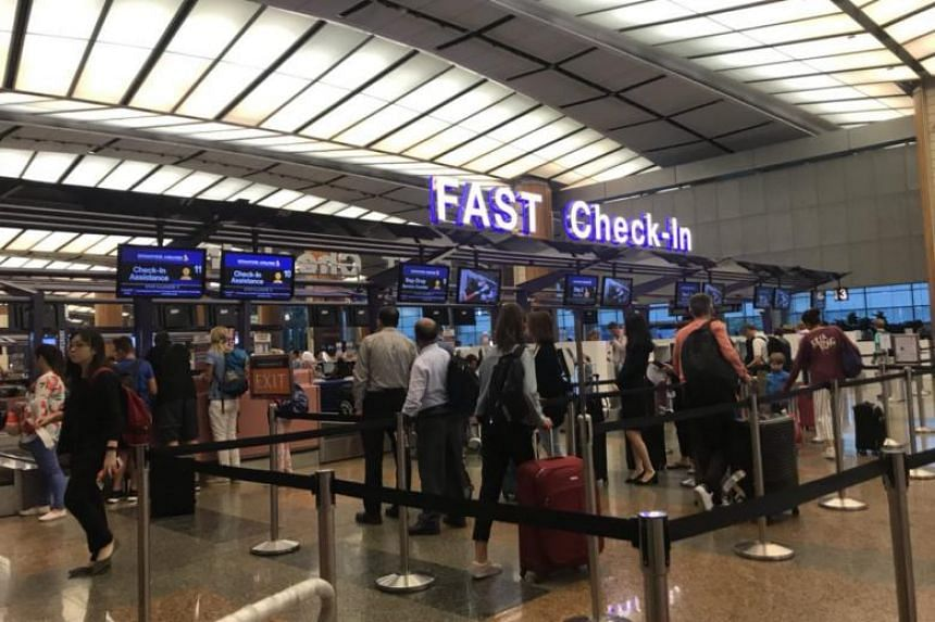 Travellers standing in line at Changi Airport, where flights to Lombok and Bali were operating as usual on Aug 6, 2018.