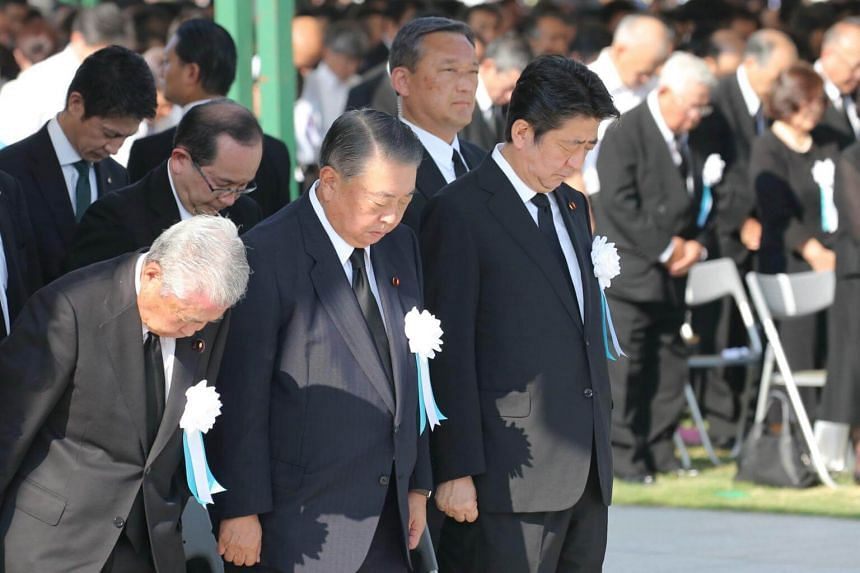 Japanese Prime Minister Shinzo Abe and officials offer a minute of silent prayers for victims of the 1945 atomic bombing during a memorial ceremony at the Hiroshima Peace Memorial Park, on Aug 6, 2018.