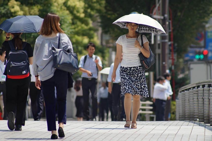 Pedestrians walking during a heatwave in Tokyo, where Typhoon Shanshan is set to bring strong winds and heavy rains later this week.
