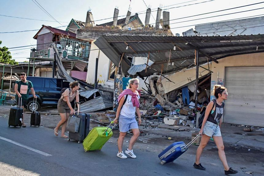 Tourists pulling their suitcases as they walk past buildings damaged by a strong earthquake in North Lombok, Indonesia, on Aug 6, 2018.