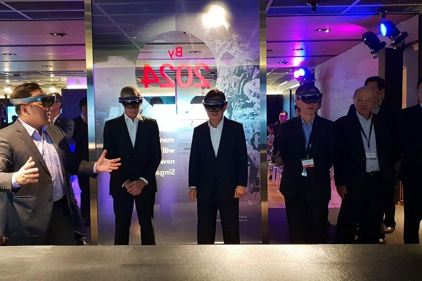 Finance Minister Heng Swee Keat (centre) using augmented reality technology to virtually see an oil and gas refinery at the Singtel FutureNow Innovation Centre, on Aug 6, 2018.