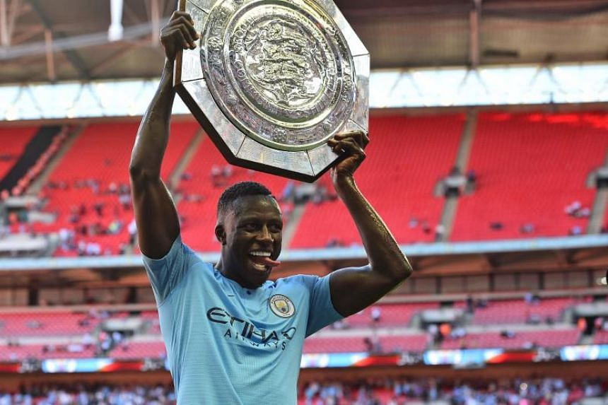 Manchester City's French defender Benjamin Mendy celebrates with the trophy on the pitch after the English FA Community Shield football match between Chelsea and Manchester City at Wembley Stadium in north London on Aug 5, 2018.