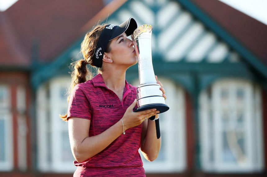 England's Georgia Hall celebrates winning the Women's British Open with the trophy at the Royal Lytham & St Annes Golf Club, Lytham Saint Annes, Britain, on Aug 5, 2018.
