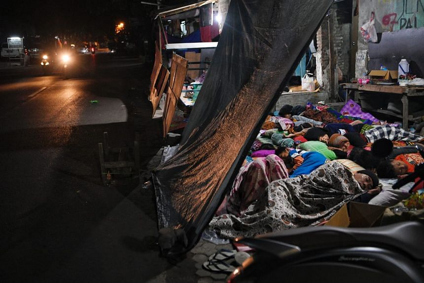 Residents sleep outside their houses in Mataram on Indonesia's Lombok island on Aug 6, 2018, a day after an earthquake struck the area.