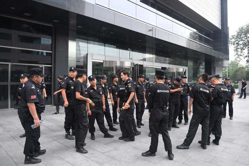 Security personnel stand in front an entrance of China's Banking Regulatory Commission in Beijing on Aug 6, 2018.
