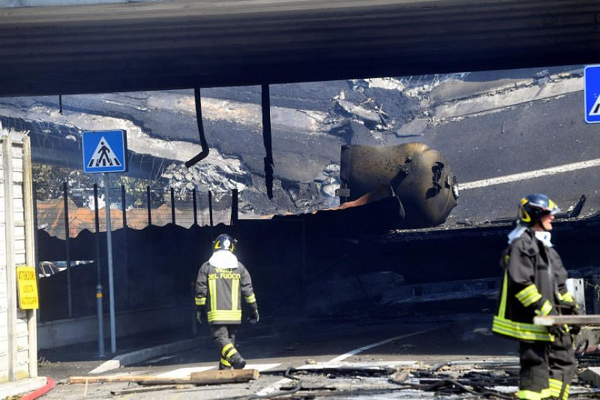 Firefighters work near the motorway after an accident caused a large explosion and fire at Borgo Panigale, on the outskirts of Bologna, Italy, on Aug 6, 2018.
