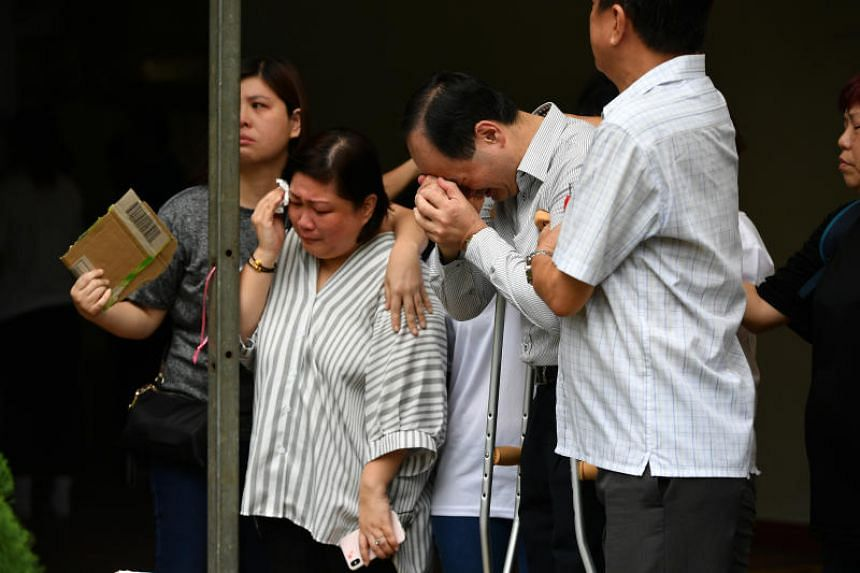 Parents of Corporal First Class (CFC) Dave Lee Han Xuan, Madam Jasmine Yeo and Mr Dennis Lee, crying before the cortege leaves the family home for Mandai Crematorium during CFC Lee's military funeral on May 5, 2018.