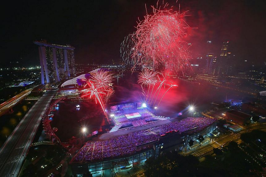 Top and above: During the NDP Preview on Sunday, fireworks lit the sky in the daytime and at night. Right: Workers preparing fireworks for an NDP rehearsal.