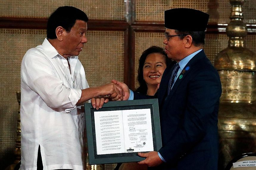 President Rodrigo Duterte presenting a document containing a signed autonomy law to Moro Islamic Liberation Front chairman Murad Ebrahim during a ceremony in Manila yesterday.