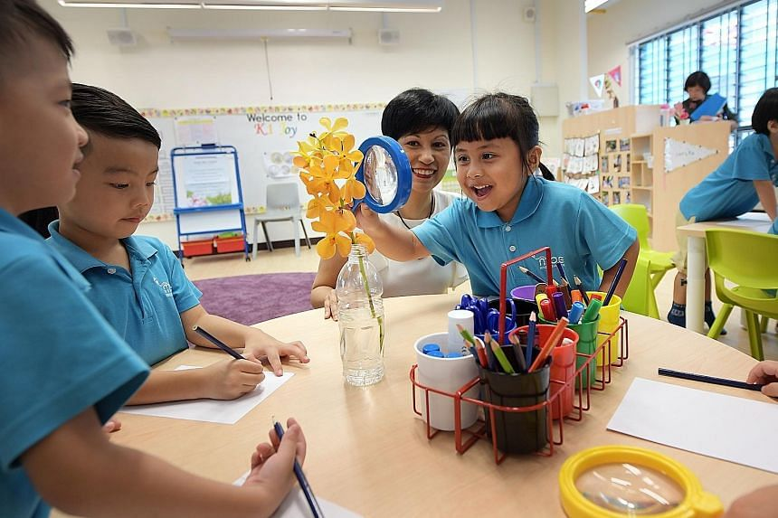 Second Minister for Education Indranee Rajah joining five-year-old Ungku Naura Fatiha Tungku Mahmood in a class activity during her visit to the MOE Kindergarten @ Punggol Cove yesterday. A third of the spaces at MOE kindergartens are allocated to Si