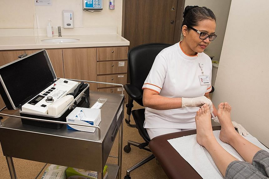 Ms Rubiah Omar, a senior enrolled nurse at Bukit Batok Polyclinic under the National University Polyclinics, conducting a foot screening with the aid of the 10g monofilament device. At the National Healthcare Group, the polyclinics under its charge h