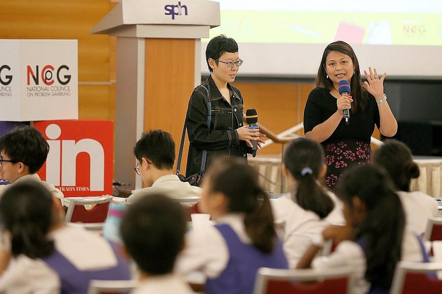 Ms Ang Yiying (left), Straits Times Schools correspondent, and Ms Shahrena Hassan, a senior manager at Singapore Press Holdings (SPH), briefing students participating in the National Youth Media Competition at the SPH auditorium yesterday.