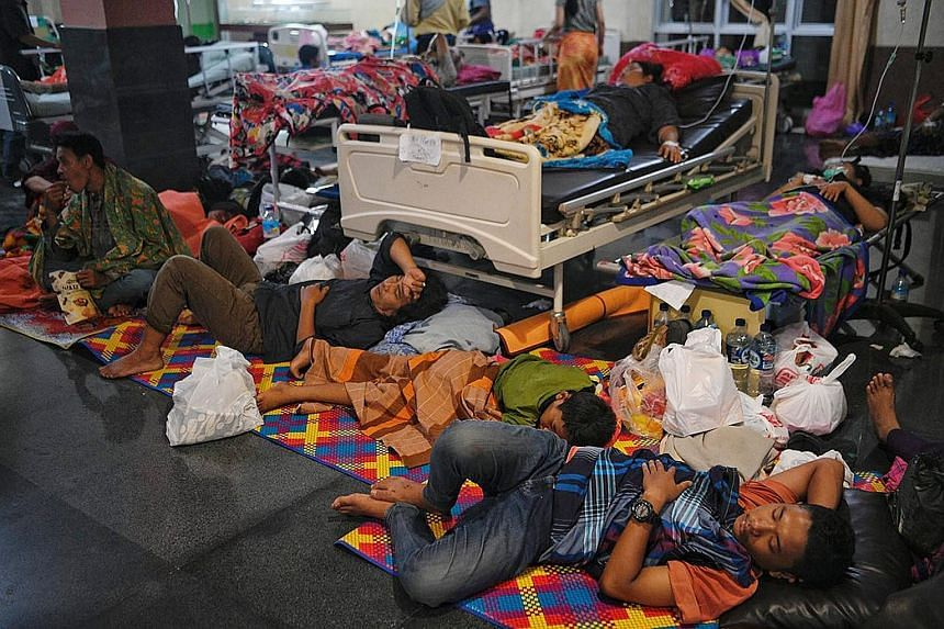 Above: Patients sleeping at the lobby of the provincial hospital in Mataram, capital of West Nusa Tenggara province, yesterday to facilitate evacuation if there are tremors. Left: Foreign tourists, with their luggage in tow, making their way past dam