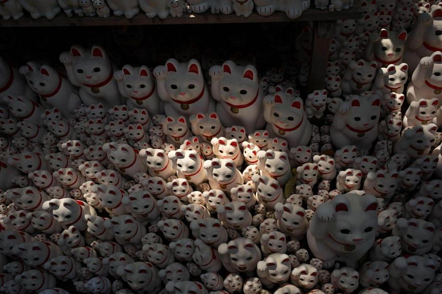 Around 10,000 figurines of white cats seated with one paw raised are stacked and strewn around the temple.