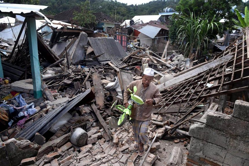 A man carrying a small bicycle through the ruins of houses damaged by an earthquake in West Lombok, Indonesia, on Aug 6, 2018.
